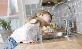 kind drinkt water uit de kraan